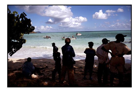 Ilôt de T'samporo, à 5km des côtes de Mayotte. 15 mn en kwassa-kwassa de traversée. Aujourd'hui, les alizées tapent fort. Des clandestins anjouanais, débarqués sans savoir sur cet îlot, attendent une aide d'urgence. Pas d'eau potable, ils vont la chercher dans un put. Ils pêchent ou vole les vergers mahorais pour survivre. Il n'y a rien sur cet îlot. Que des champs de culture (bananes, oranges,..) appartenant à des locaux majorais. Ils sqauttent même leurs bangs.Pour certains cela fait un mois qu'ils y végètent, sans rien pouvoir faire.Soit ces clandestins ont un numéro familial sur Mayotte et essayent de récolter la somme de 50 à 300 euros pour les faire passer de l'autre côté . Pour d'autres, sans aucune attache, ils disent même attendre la Paf pour les sauver et les ramener à Anjouan. Cet après-midi là, des clandestins regardent l'évacuation d'un des leurs, bléssé lors de leur voyage en kwassa depuis anjouan.  Bras cassé. Les pompiers prévenus par la police viennent le secourir pour l'amener au plus proche. Et il sera évacué vers l'hôpital de Mamoudzou puis surement reconduit. 3 juin 2012.