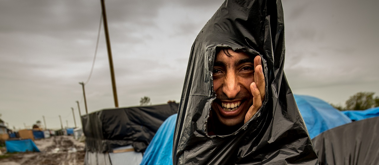 "A migrant, who protects himself from the rain with a plastic trash bag, walks through a mudpath of the ""New Jungle"" migrant camp in Calais, where thousands of migrants live in the hope of crossing the Channel to Britain, on October 21, 2015. European Commission chief Jean-Claude Juncker has called a mini-summit in Brussels on October 25 to tackle the migrant crisis along the western Balkans route, his office said. AFP PHOTO / PHILIPPE HUGUEN / AFP PHOTO / PHILIPPE HUGUEN"