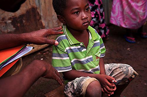 """Commune de Vahibé, prés de Mamoudzou, où 90 % de la population depuis des années est anjouanaise, précaire, clandestin, vivant dans des bangas. Des mineurs isolés en grand nombre, en précarité alimentaire et sanitaire. Mdm intervient en clinique mobile fixe. Anfahidine est un mineur de 4 ans, isolé, recueilli par sa voisine qui ne préfére pas témoigner à visage découvert et de vive voix. C'est une précaire aussi et l'a recueilli parce que son père il y a deux mois a été pris par la paf et reconduit à Anjouan.  """"C'est mon devoir; Je ne sais pas si les autres font comme ça ou s'il y a d'autres enfants isolés. Mais c'était tout à fait naturel."""".Le travailleur social de MDM le suit depuis lors.  24 mai 2012, Mayotte."""